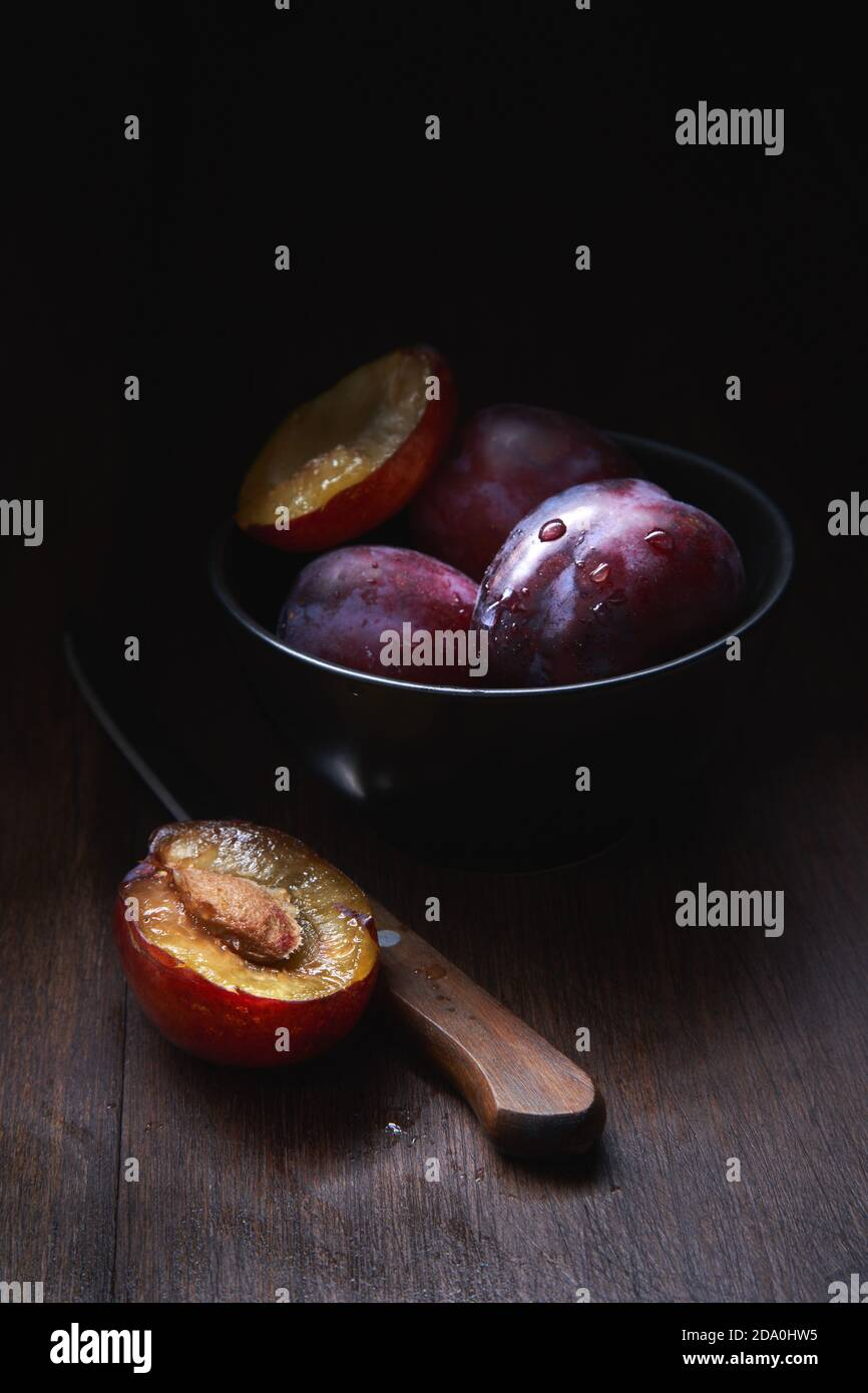 Still life composition with bowl with ripe aromatic juicy plums with water drops arranged on wooden table with knife and halved fruit Stock Photo