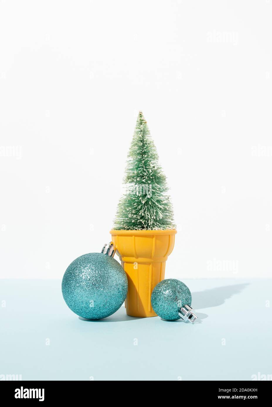 Artificial Spruce Branches Decorated With Silver Christmas Baubles Placed In Ice Cream Cup On Table In Studio On Blue Background Stock Photo Alamy