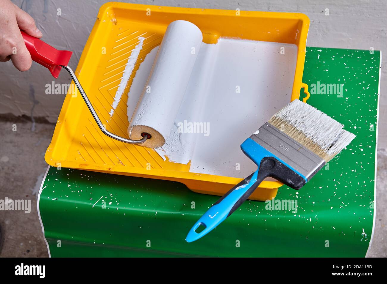 Construction painting supplies for home repair, paint roller and paintbrush into tray with dye. Stock Photo