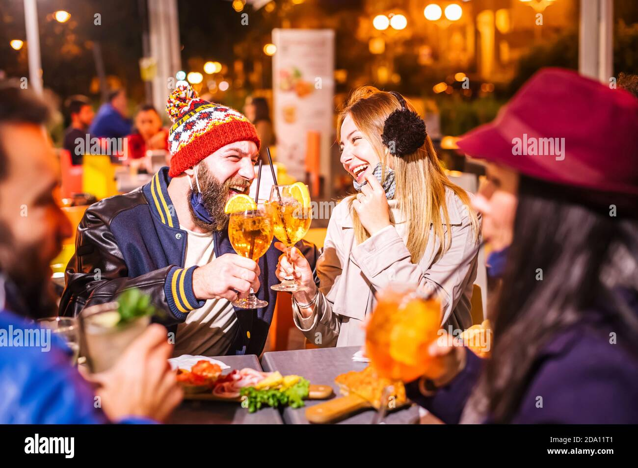 Man and woman smiling and toasting spritz at winter cocktail bar outdoors wearing open face mask - New normal lifestyle concept with millennial people Stock Photo