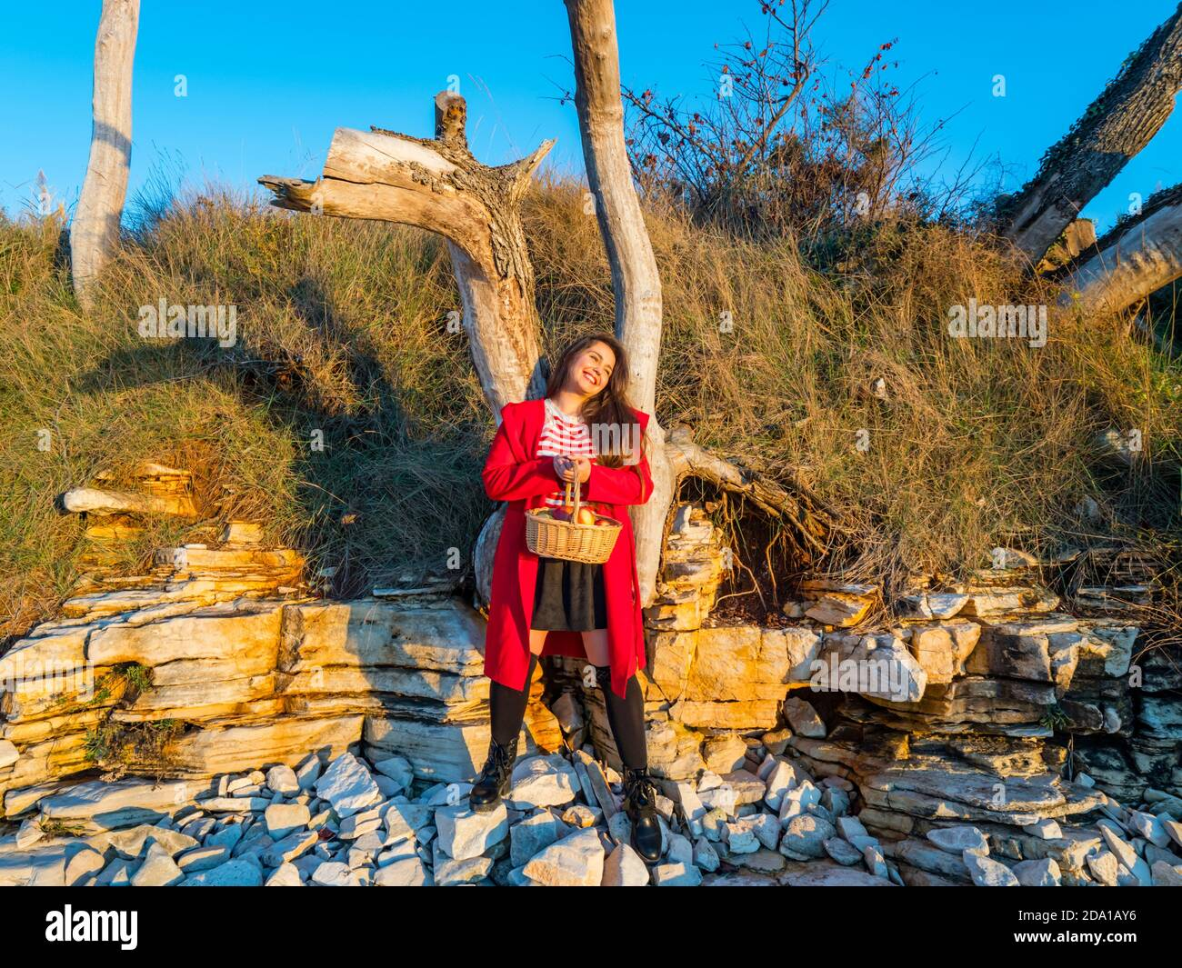 Young woman aka little Red Riding Hood with pastoral wicker basket in hand standing happy smiling looking away aside Stock Photo