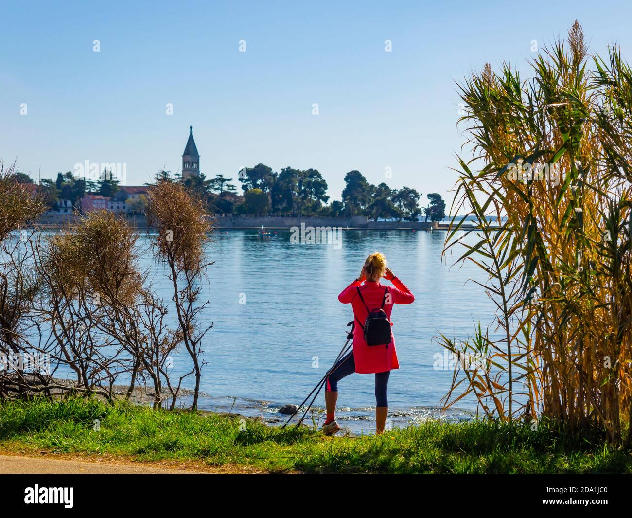 Croatia Novigrad oldtown old town in Istria tourist female young woman in Red clothing walker sticks Stock Photo