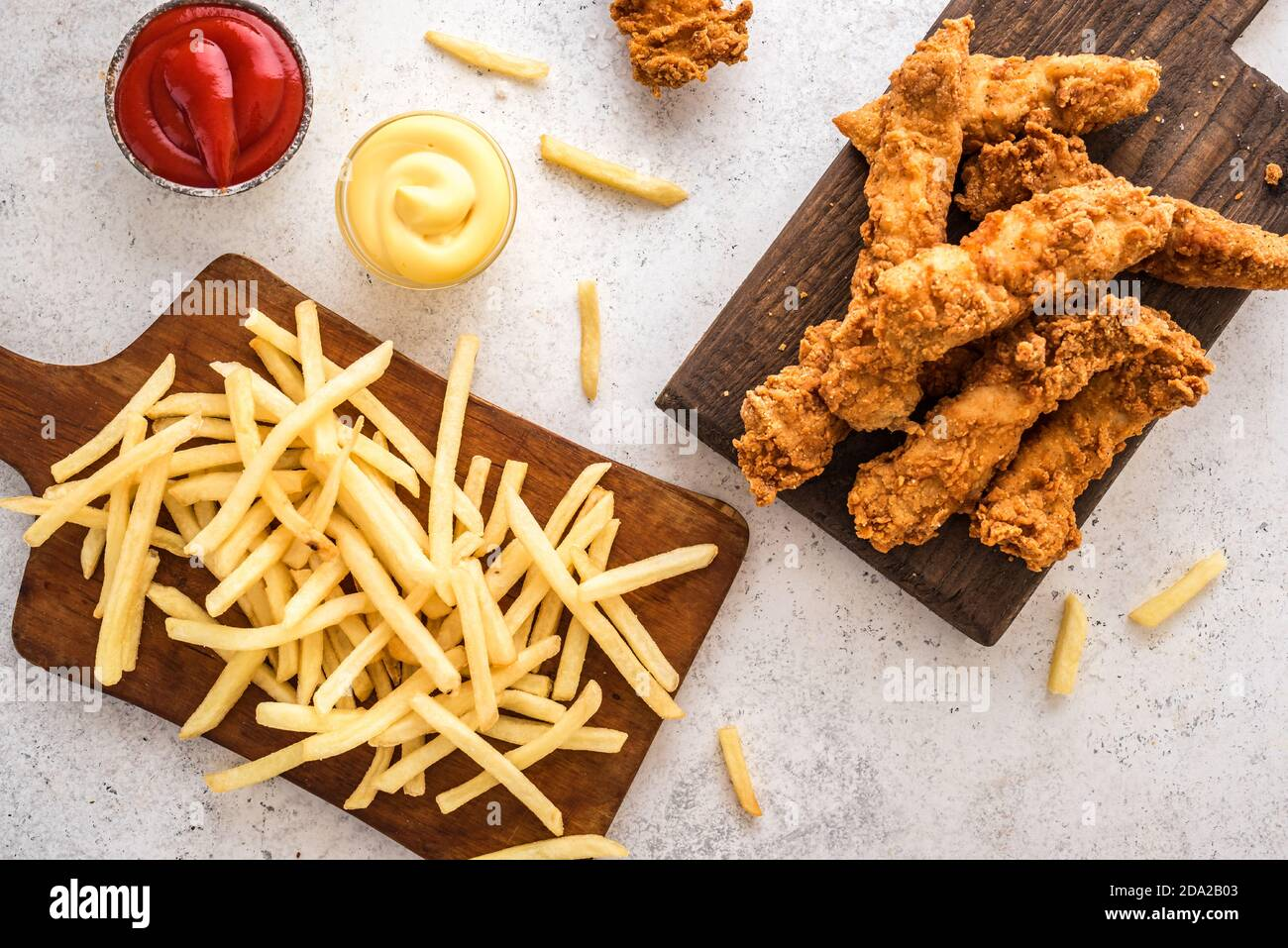 Fish and chips. Deep fried fish filet and with french fries on white background with sauces. Traditional british street food. Stock Photo
