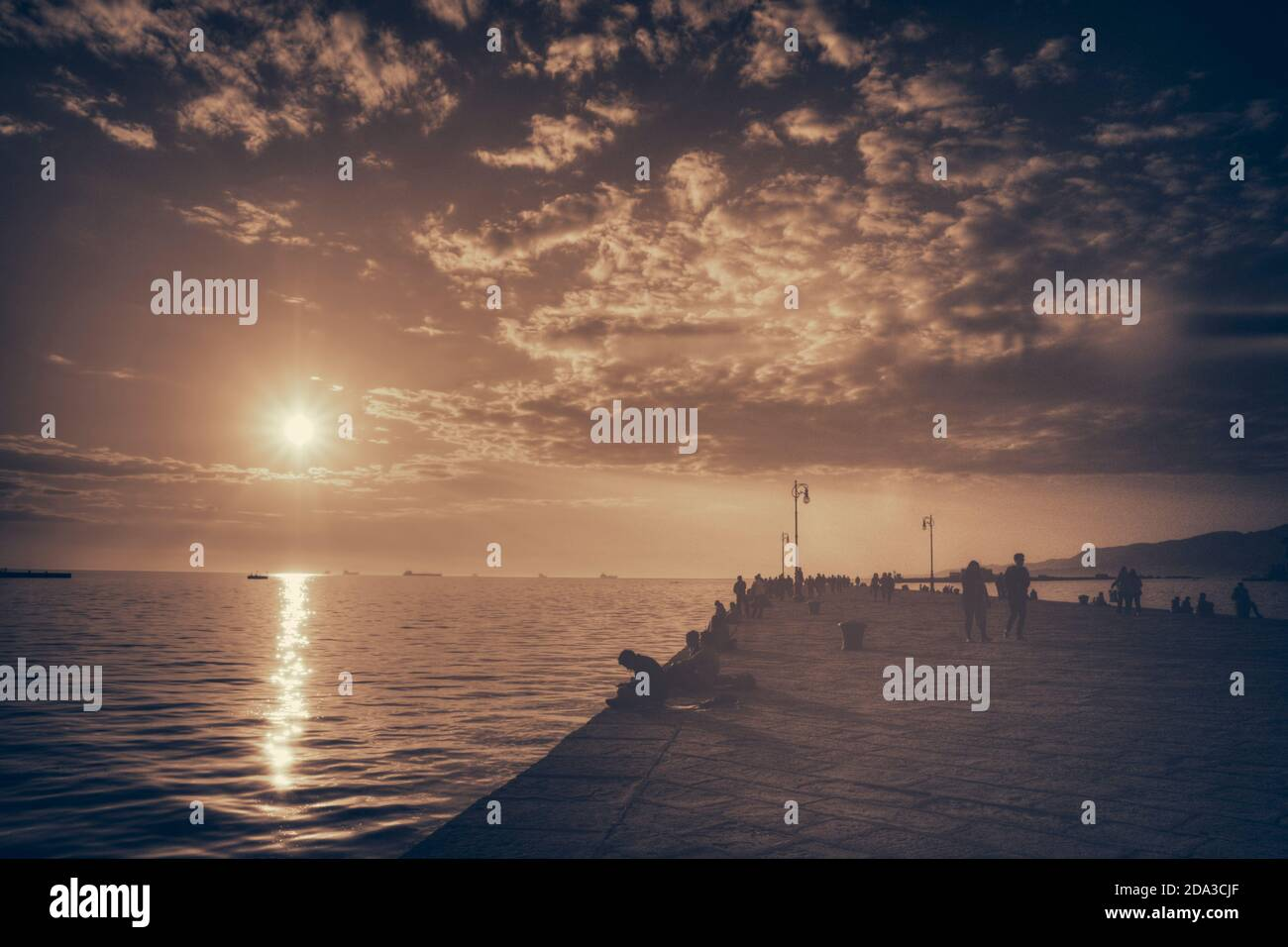Trieste, Italy. Molo Audace. People relax in the warm light of a romantic sunset Stock Photo