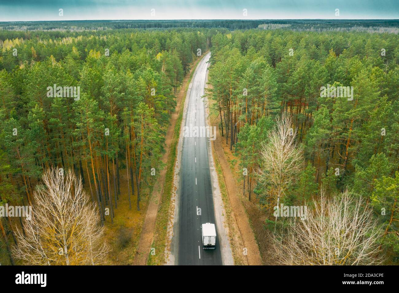 Aerial View Of Highway Road Through Spring Forest Landscape. Top View Of Truck Tractor Unit Prime Mover Traction Unit In Motion On Freeway. Business Stock Photo