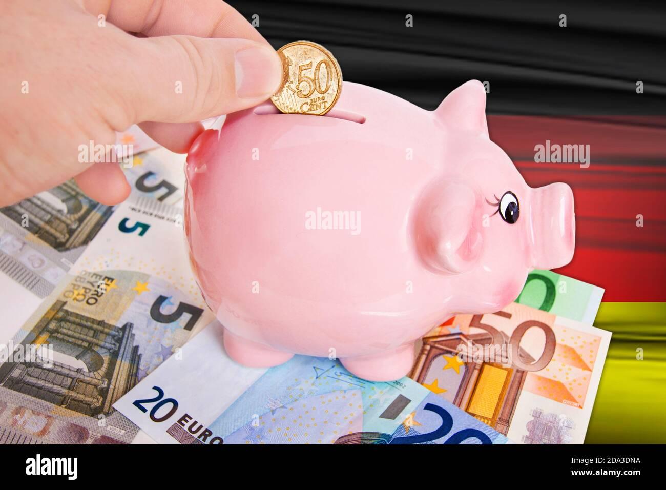 Sparschwein mit 50 Cent Euromünze auf  Deutschlandflagge Stock Photo