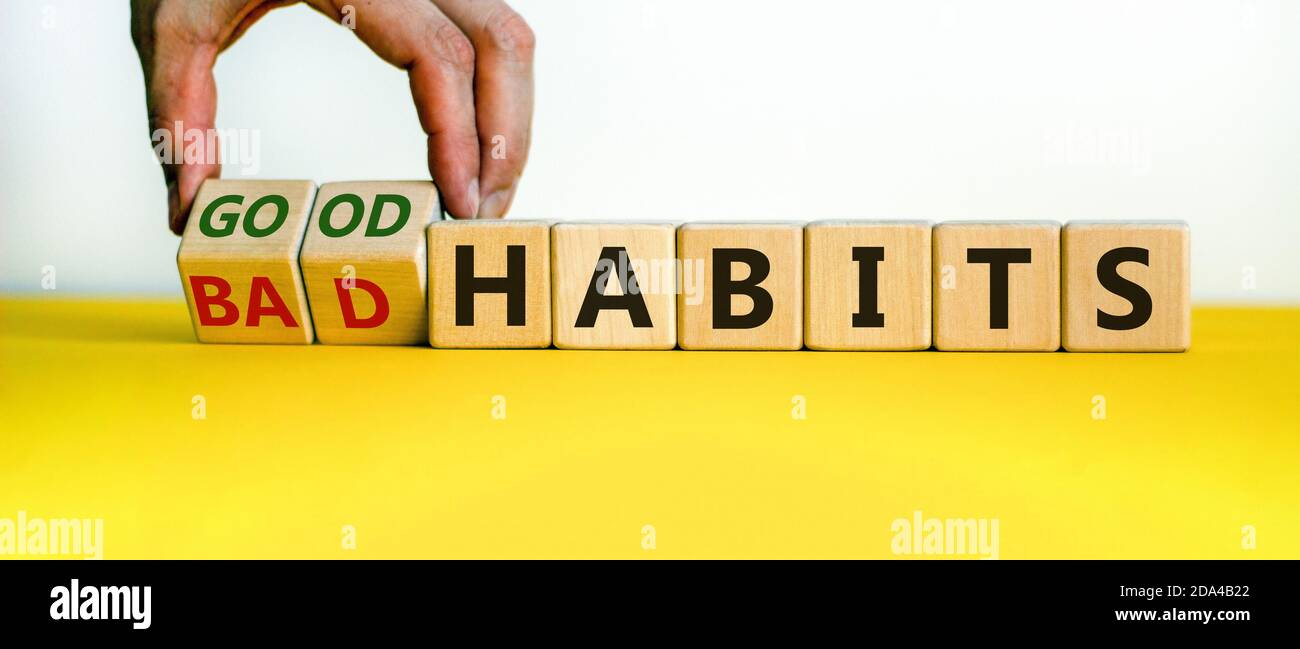 Male hand turning cubes and changes the expression 'bad habits' to 'good habits'. Beautiful yellow table, white background. Concept. Copy space. Stock Photo