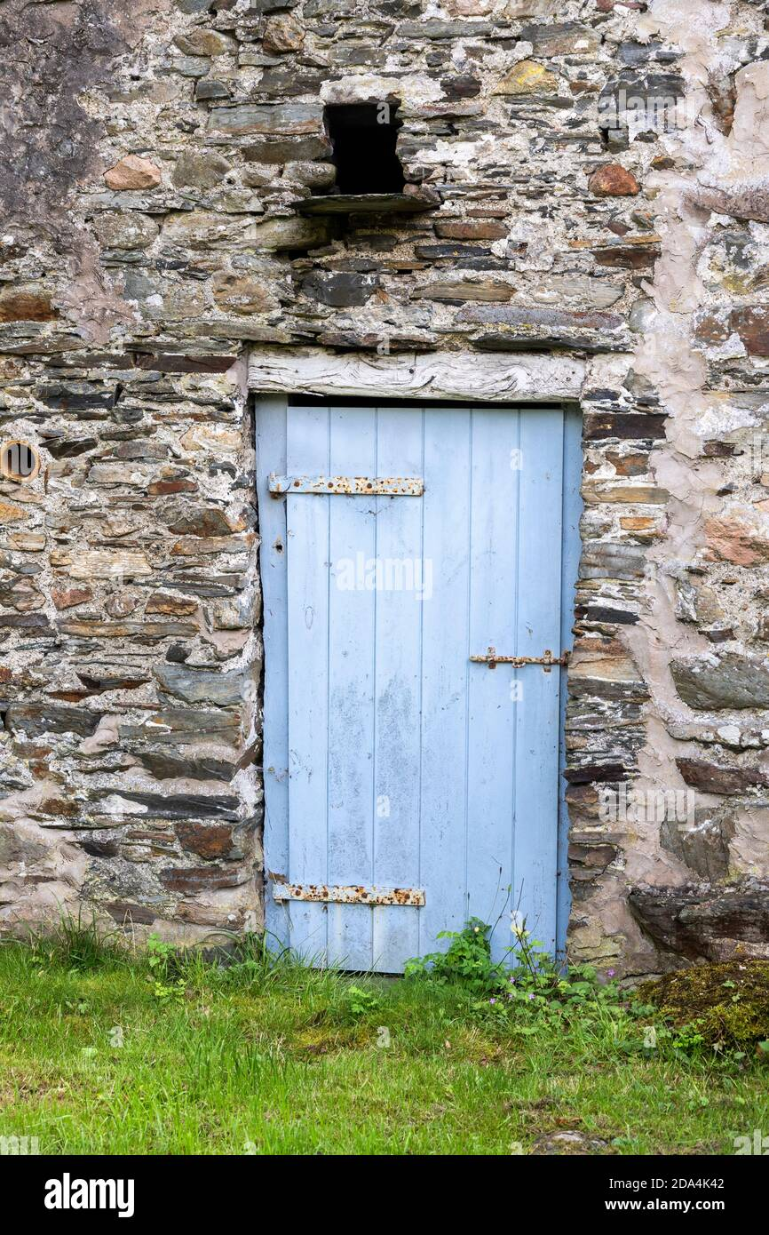 An old wooden door in a traditional stone farm building at Lowpark in the English Lake District near Loweswater, Cumbria UK Stock Photo