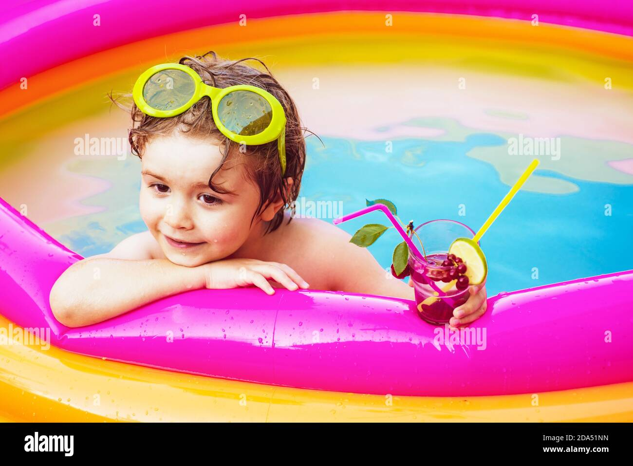 Little child boy having fun in the pool. Cute kid relaxing on swimming pool. Children playing in pool. Child water toys. Cocktails drinks. Stock Photo