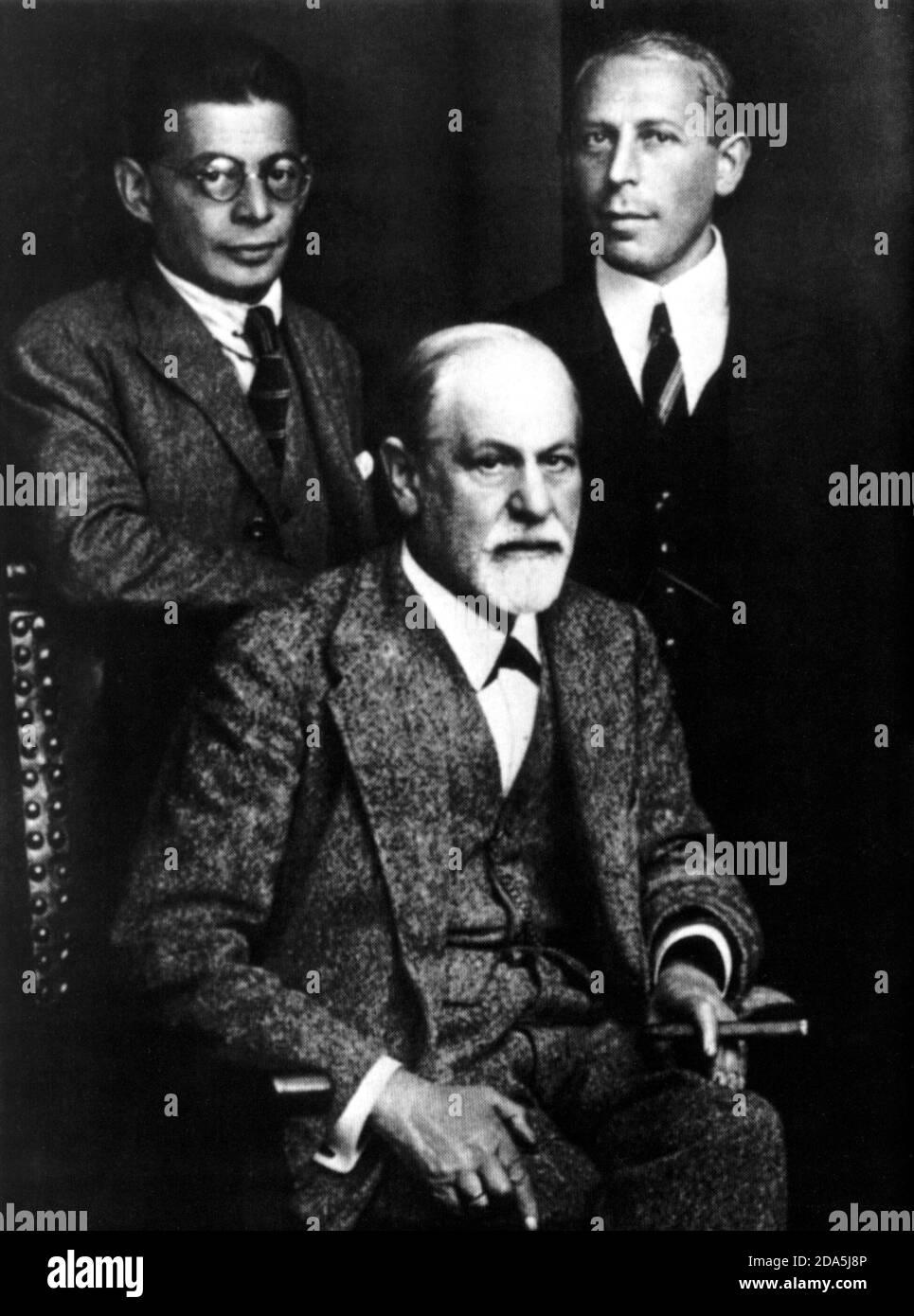 1922 , AUSTRIA  :The austrian father of psychoanalysis  SIGMUND FREUD  (  1856 -   1939 ) with assistants  OTTO RANK ( stand at left ) and  KARL ABRAHAM  - PSYCHOANALYST - PSICANALISTA - PSICOANALISTA - PSICANALISI - PSICOANALISI - ebreo - jewish  -  RITRATTO - PORTRAIT - collar - colletto - tie - cravatta -  papillon - barba bianca - white beard - uomo anziano  vecchio - older old ancient man - SCIENZIATO - SCIENTIST - genio - genius - occhiali - glasses - stempiato - stempiatura - thinning at the temples -  cigar - fumo - fumatore - smoke - smoker - personalità che fuma - celebrity - persona Stock Photo