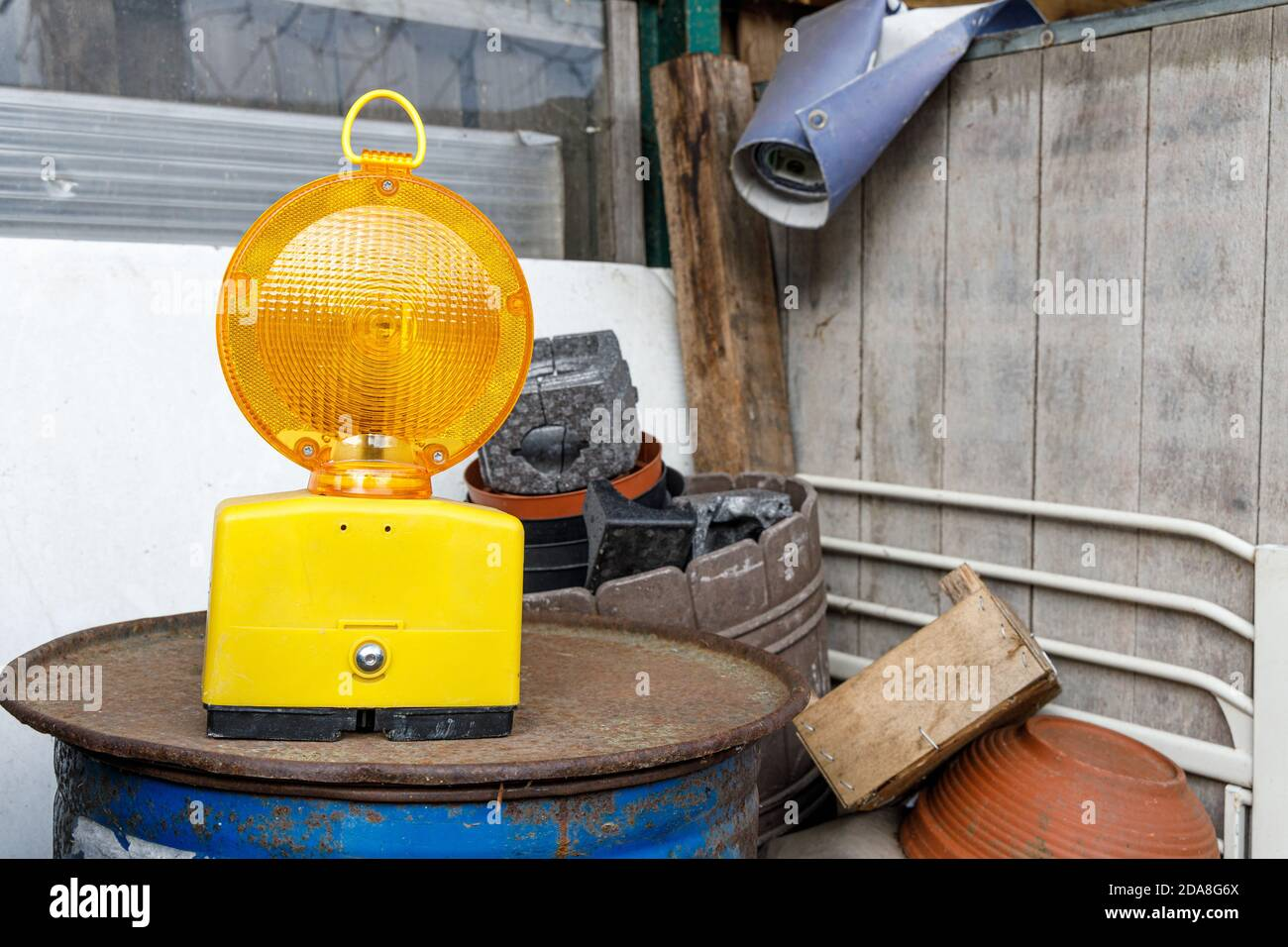 Yellow construction lamp standing on a oil barrel on a junk yard. Symbol of construction in a chaotic situation, use as site not found image. Stock Photo
