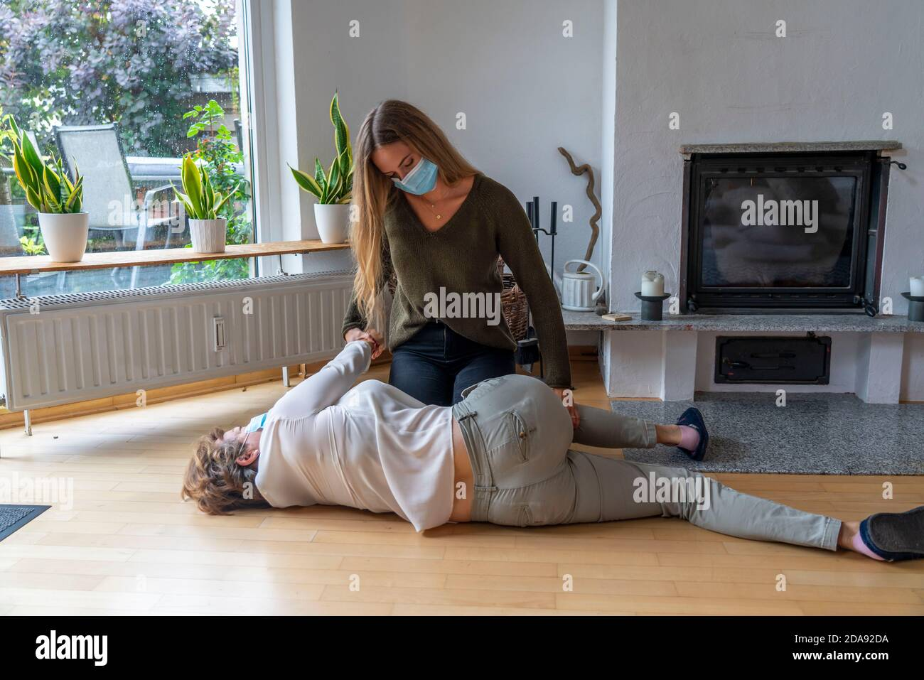 First aid measures under corona conditions, stable lateral position, after an accident in the home, with a mouth and nose mask, when first aid is give Stock Photo