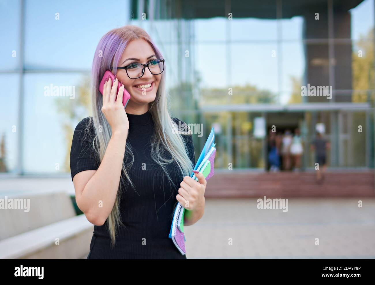 Smiling young student girl from z generation standing in a campus in front of a university building facade and talking on smartphone Stock Photo