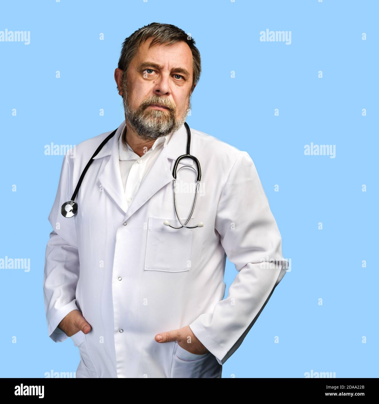 Portrait of handsome tired medical doctor with stethoscope in white coat isolated on blue background with copyspace Stock Photo