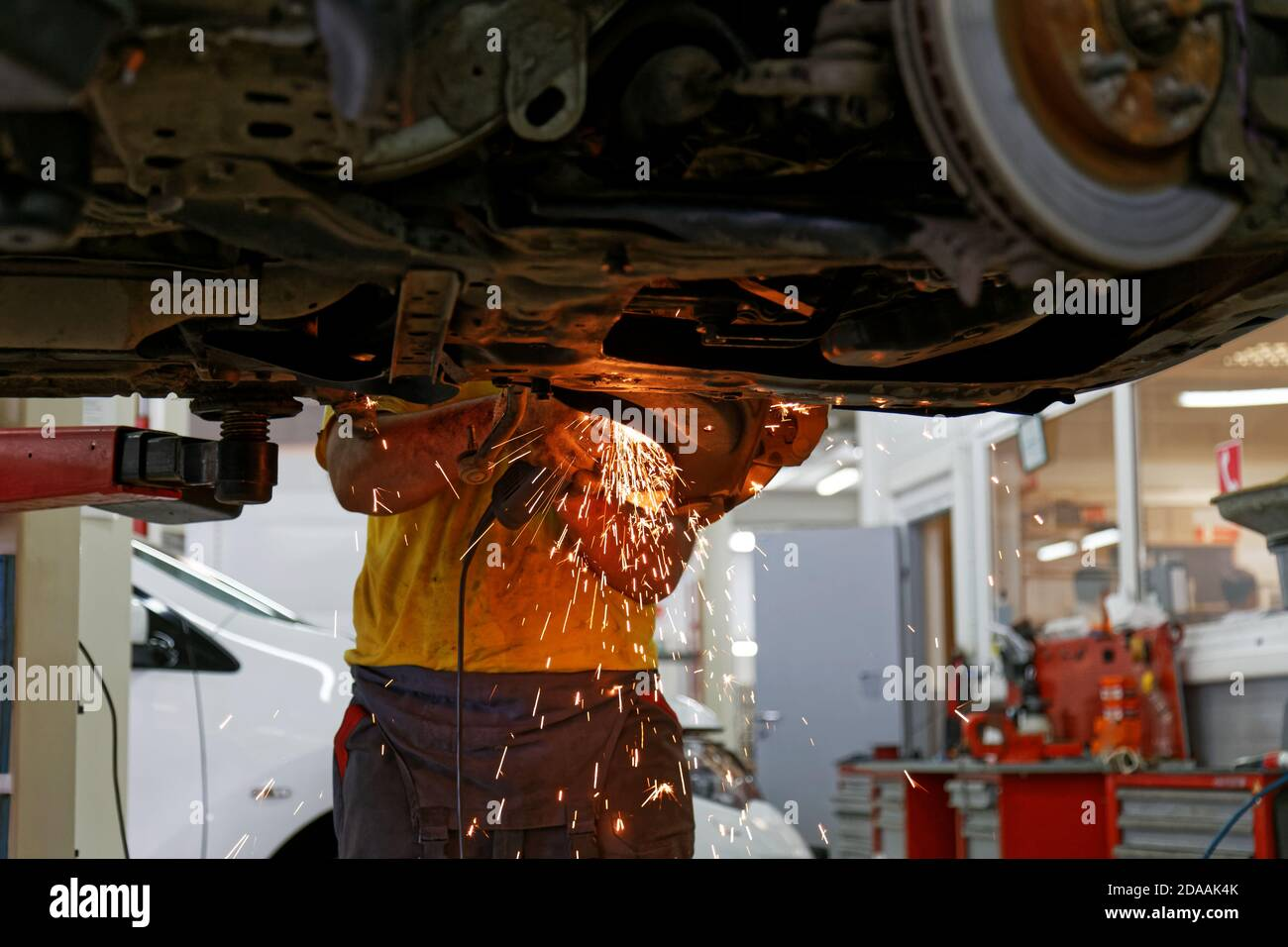 Worker of car service cleans old metal parts from rust using angle grinder. Sparks are flying in different directions. Stock Photo