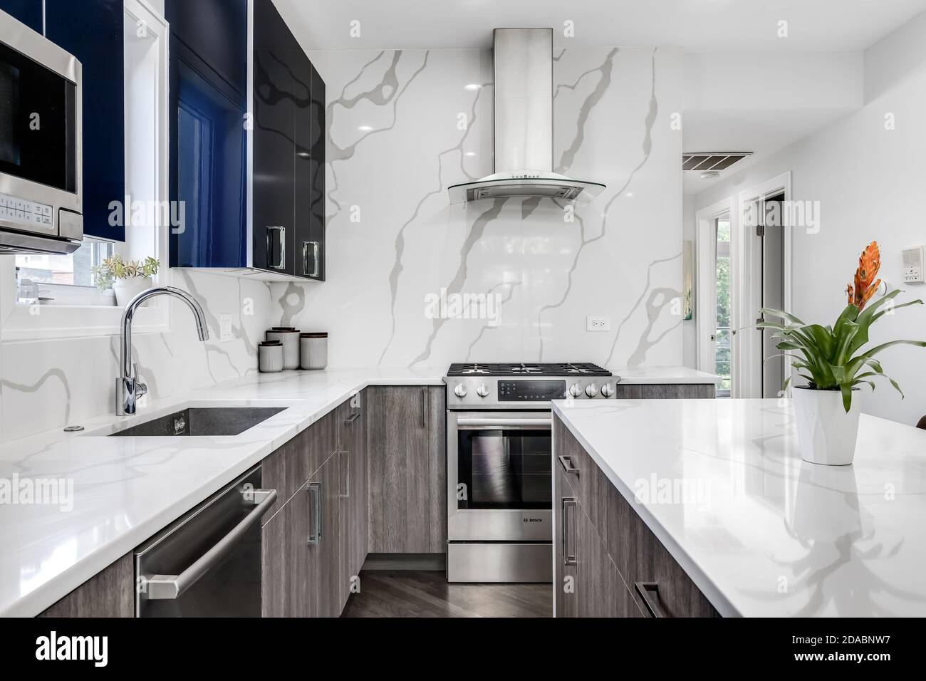 A Modern Kitchen With Blue And Wood Two Toned Cabinets With A White Marble Waterfall Island Top And Backsplash Stock Photo Alamy