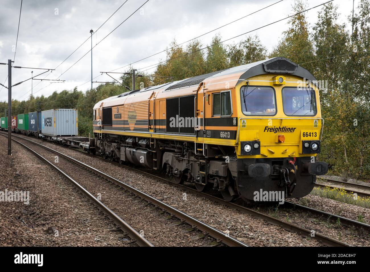 DONCASTER, UK - OCTOBER 15, 2020. A Freightliner Class 66 locomotive and Intermodal Shipping container freight train moving cargo boxes to UK ports Stock Photo