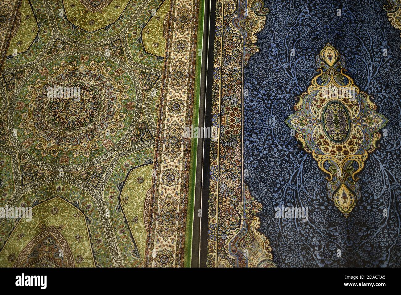 Closeup of colourful green and blue handmade Turkish carpets with intricate patterns and designs, Istanbul, Turkey Stock Photo