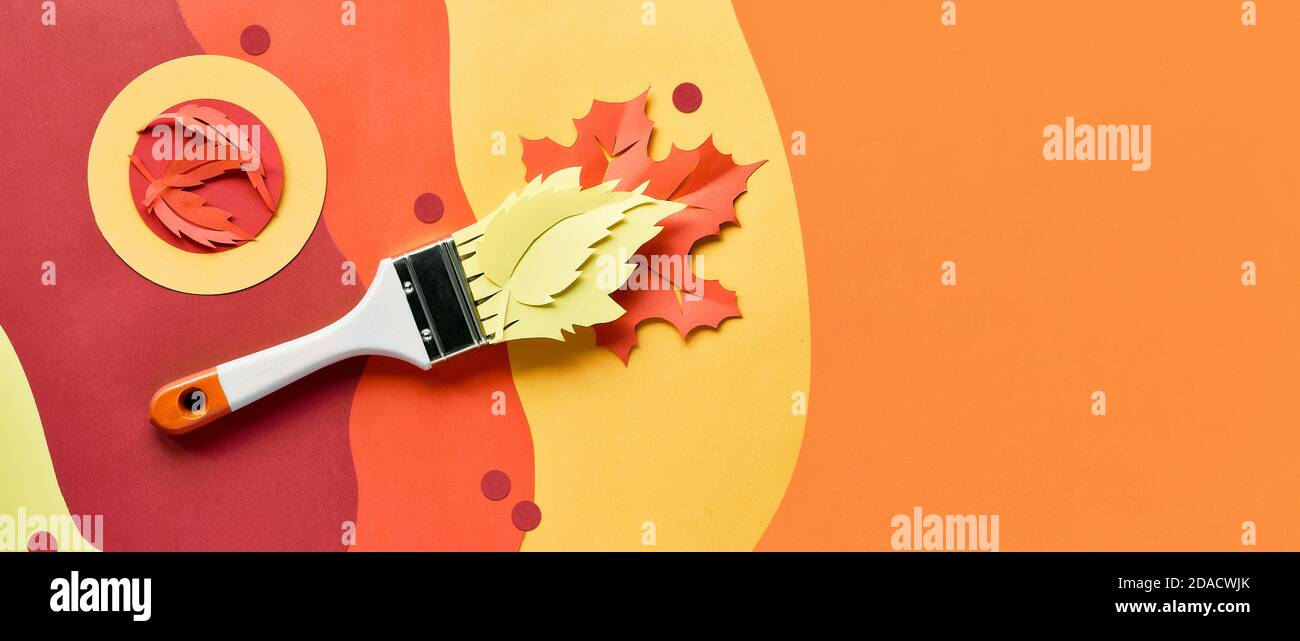 Brush loaded with paint made of paper Autumn leaves. Home renovation panoramic background, top view. Stock Photo