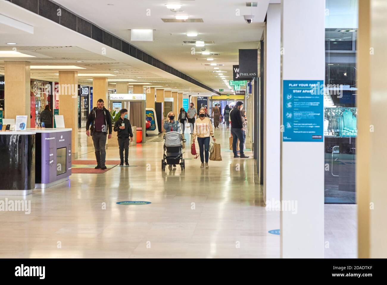 People in shopping mall at Central Milton Keynes most wearing face coverings but some are not Stock Photo