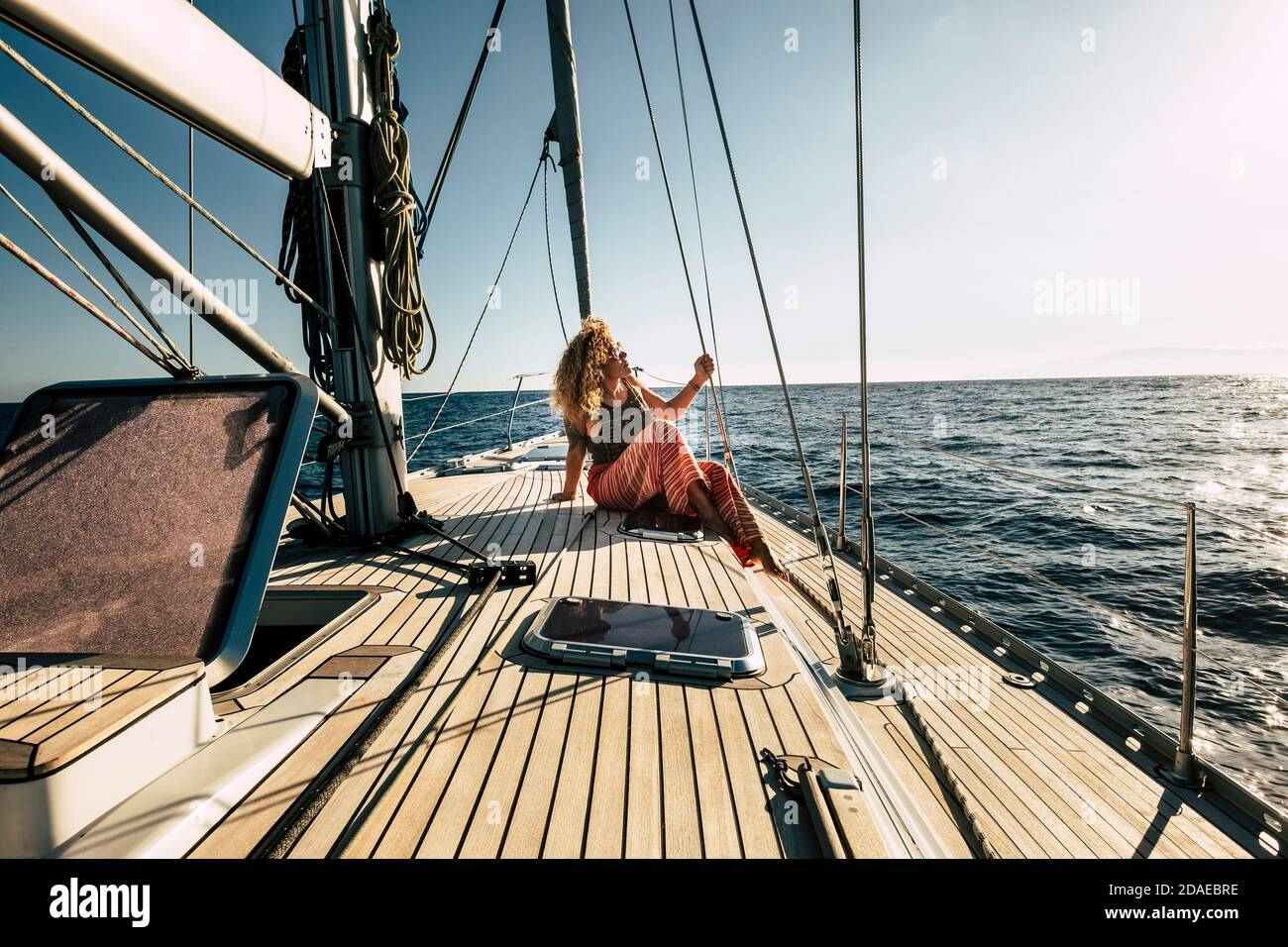 Beautiful young woman enjoy summer holiday vacation or excursion on sailboat with sun and ocean around - people enjoying life and lifestyle - travel and transport on sea concept Stock Photo