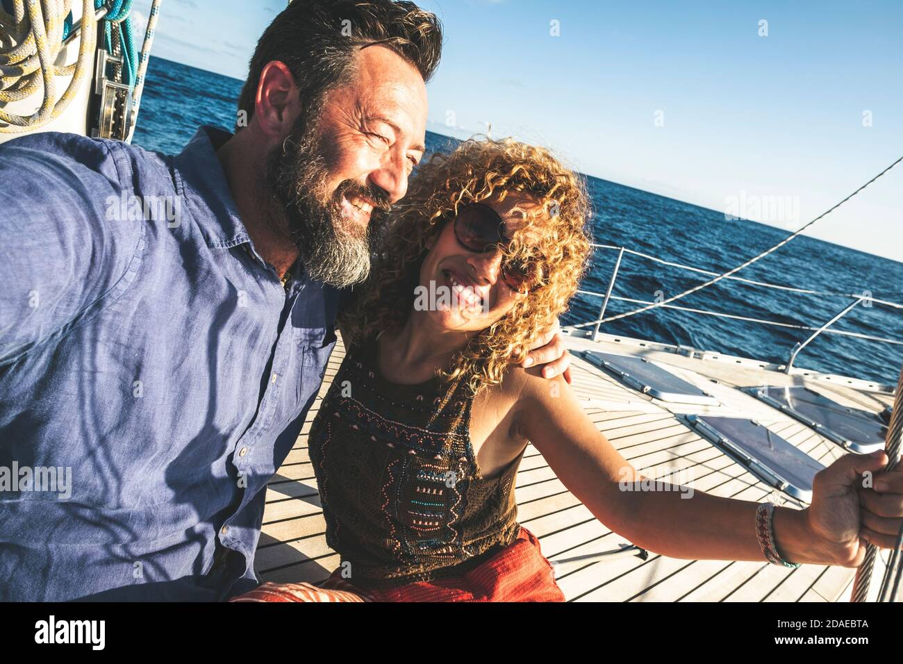 Happy adult caucasian couple together on a sailboat enjoy vacation or excursion - people in outdoor leisure activity on boat with blue ocean and sky around . happiness and love man and woman Stock Photo