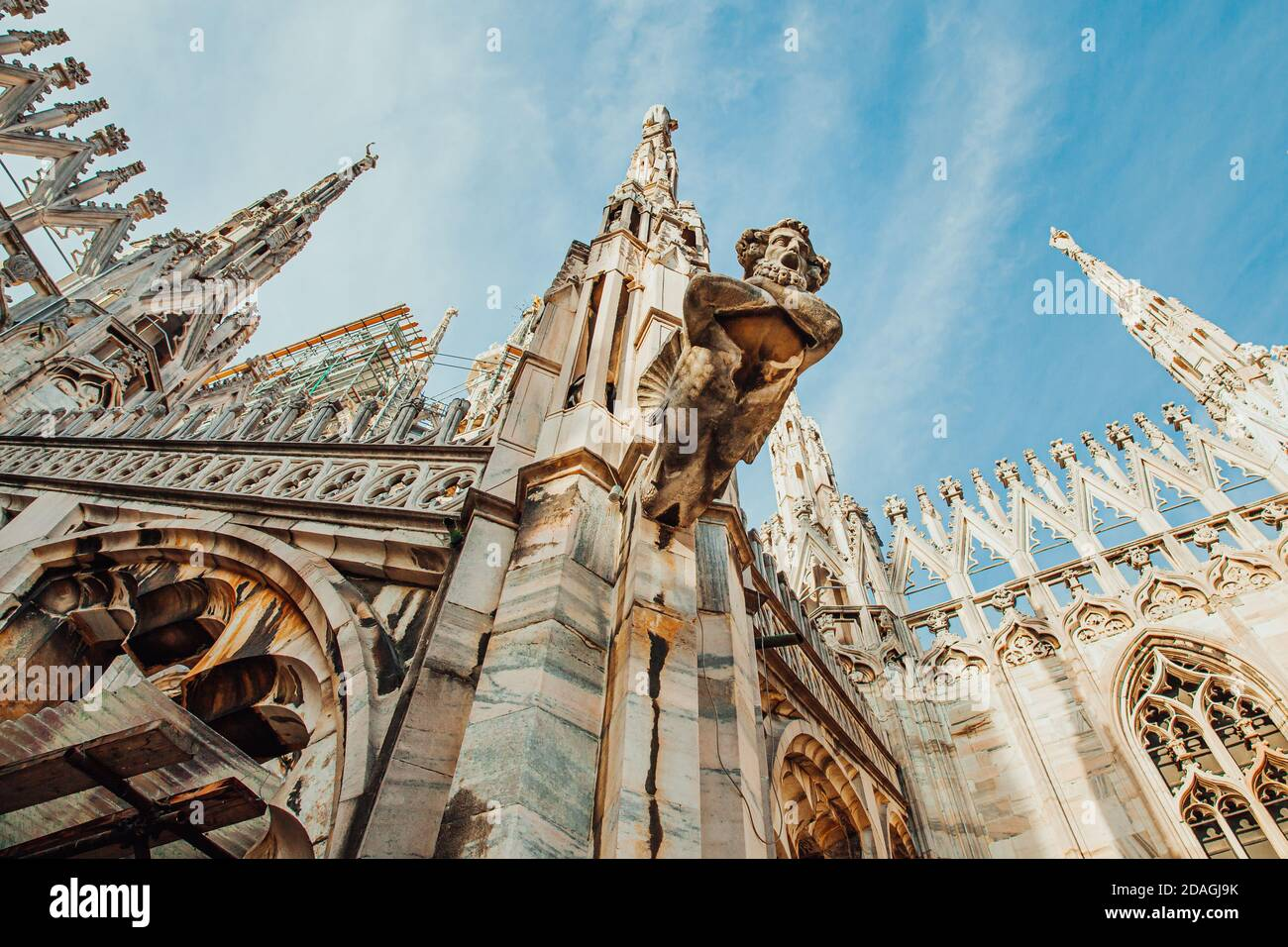 Roof of Milan Cathedral Duomo di Milano with Gothic spires and white marble statues. Top tourist attraction on piazza in Milan, Lombardia, Italy. Wide angle view of old Gothic architecture and art Stock Photo