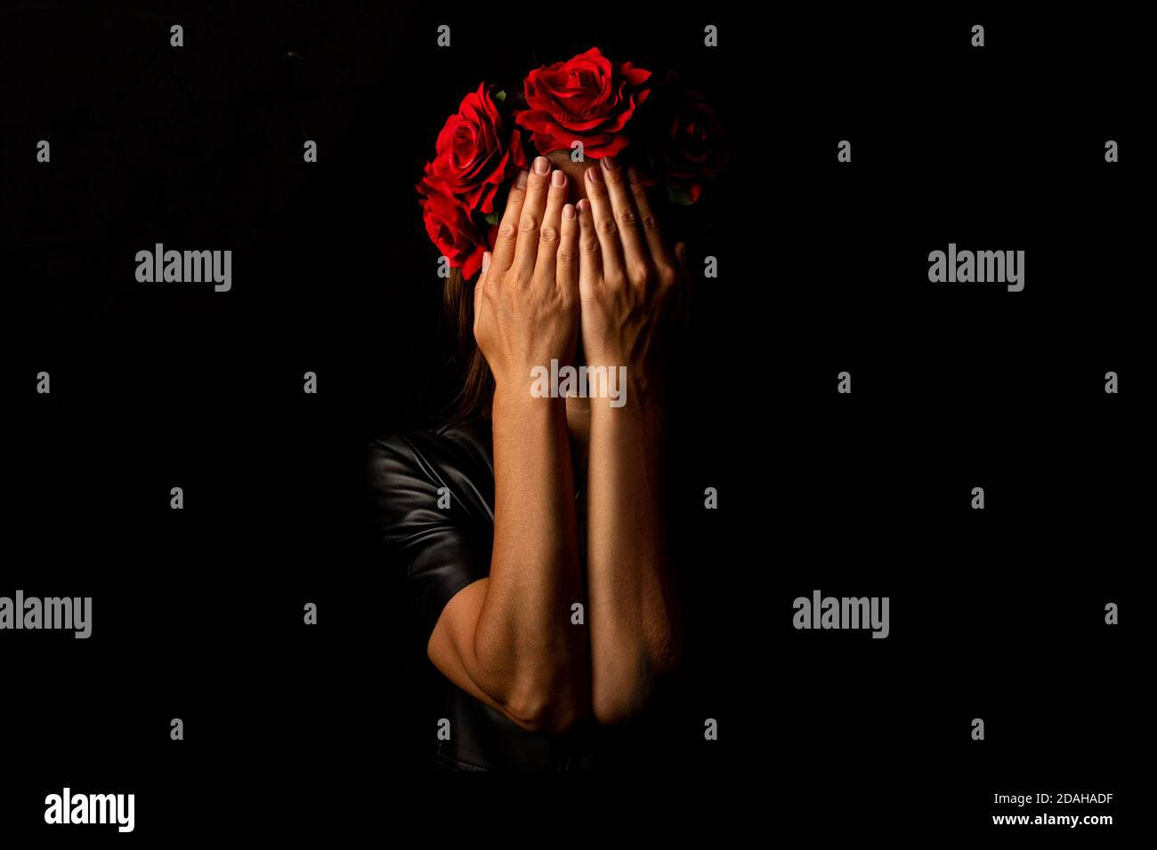 Young woman in a wreath of flowers, covering her face with her palms on a black background. Stock Photo