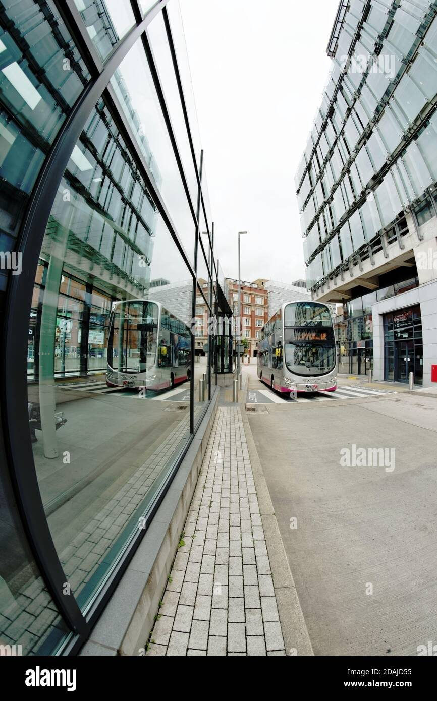 The Shudehill Interchange in Central Manchester provides a bus station and a metrolink (tram) stop. A bus and buildings are reflected in its windows. Stock Photo