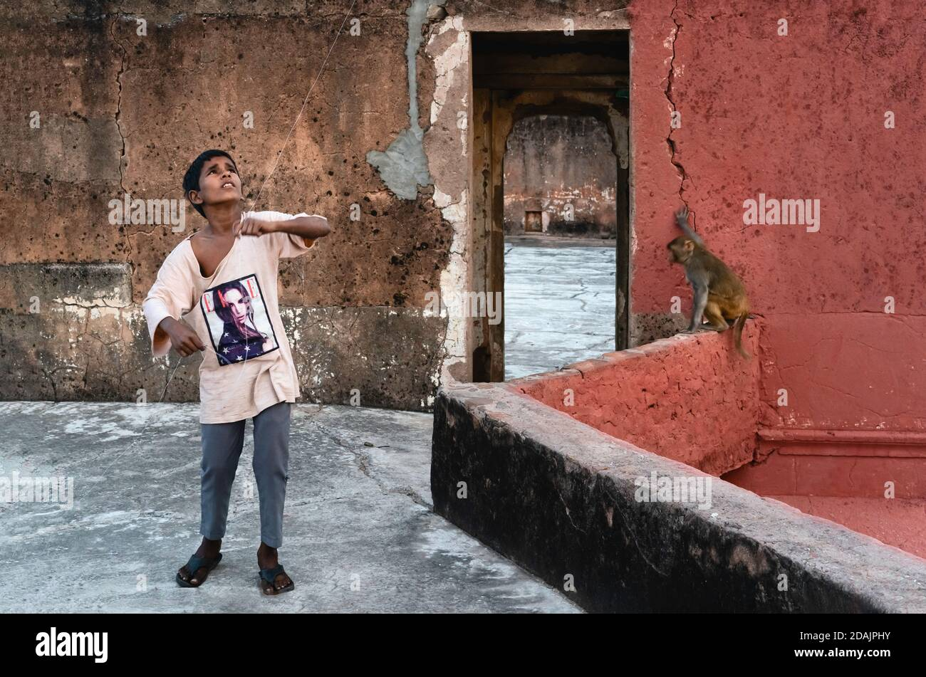 Young boy surrounded by ruins on rooftop flying kite (not in view) at dusk on November 09, 2019 in Jaipur, Rajasthan, India. Stock Photo