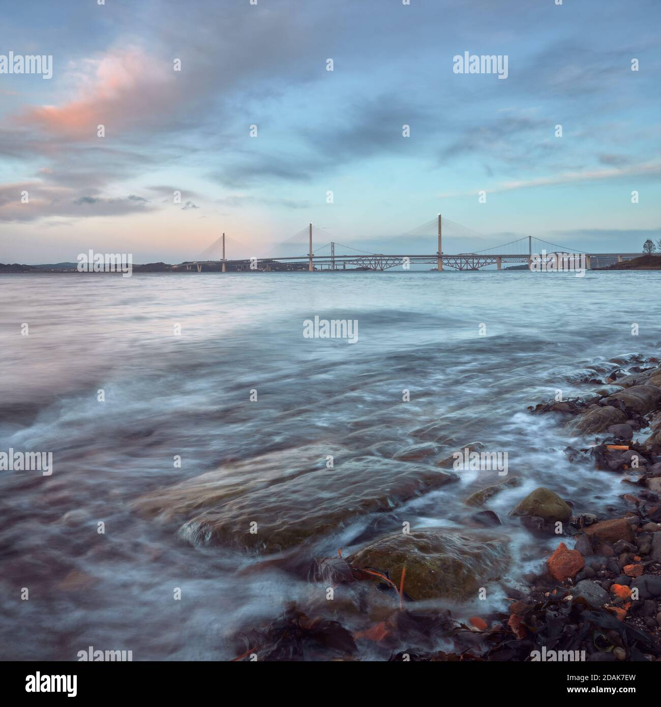A coast of the sea bay with stones at sunset near New Queensferry Crossing Bridge in Scotland Stock Photo
