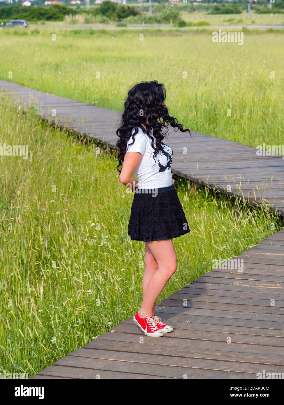 Young woman aka teen teenager standing in wooden walkway in nature looking away hidden identity obscured face anonymous nobody waiting wait hands back Stock Photo