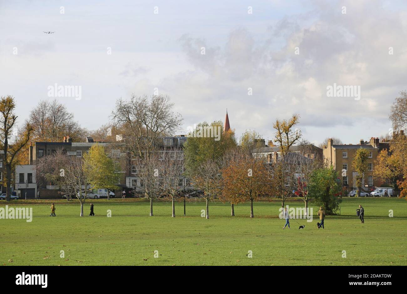 Walkers cyclists and dog-walkers enjoy a sunny autumn day on Peckham Rye Common, south east London, UK. Stock Photo