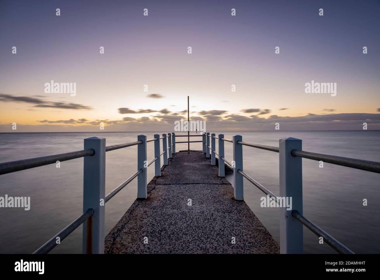 Looking out over a pier against the ocean, a purple dusk horizon sky Stock Photo