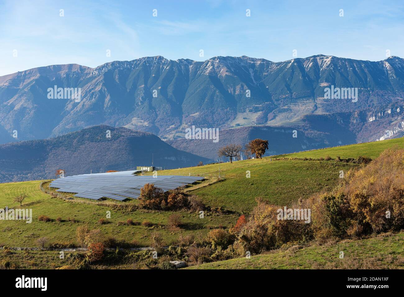 Solar power station in Italian Alps with many solar panels, Lessinia Plateau with the Mountain range of Monte Baldo. Italy. Renewable Energy concept. Stock Photo