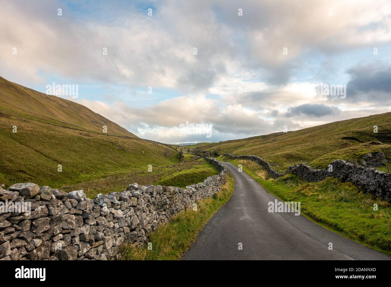 UK landscape: View looking north up the picturesque country lane of Barbondale Road, lined with drystone wall, Cumbria - Yorkshire Dales National Park Stock Photo