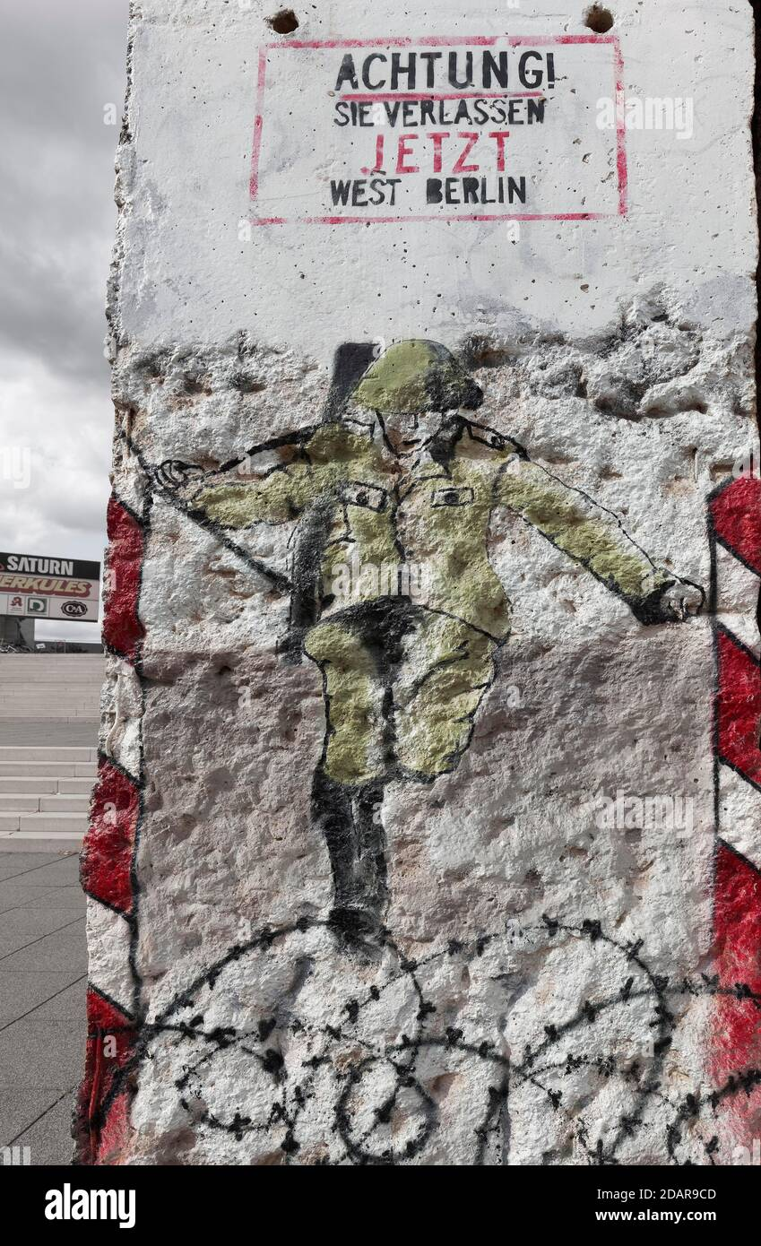 GDR border guard jumps over barbed wire to the West, graffito on a fragment of the Berlin Wall, Weimar, Thuringia, Germany Stock Photo