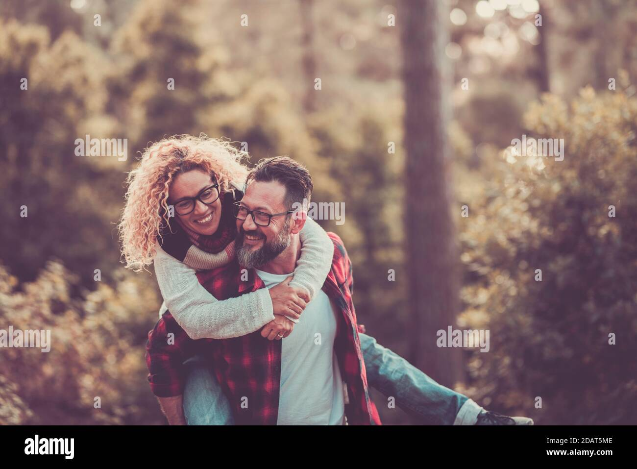 Happy adult couple enjoy nature wood forest together and outdoor leisure activity with fun and joyful - man carry woman on his back and both laugh a l Stock Photo