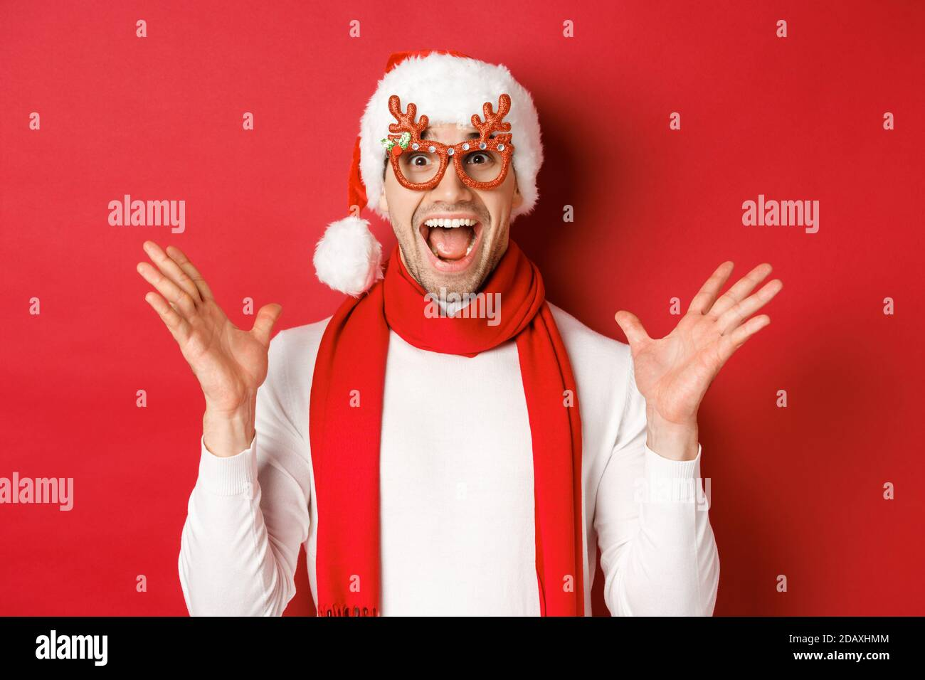 Concept of christmas, winter holidays and celebration. Image of surprised and happy man looking amazed, wearing party glasses and enjoying new year Stock Photo