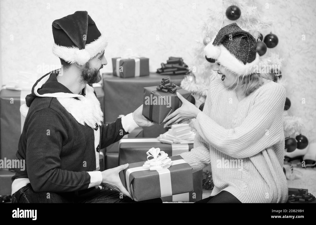 Opening christmas present. Couple in love happy enjoy christmas holiday celebration. Loving couple cuddle smiling while unpacking gift christmas tree background. Family prepared christmas gifts. Stock Photo