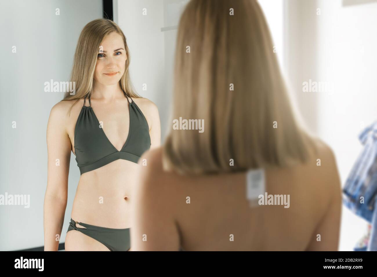 Girls in dressing room try on fashionable new bikinis