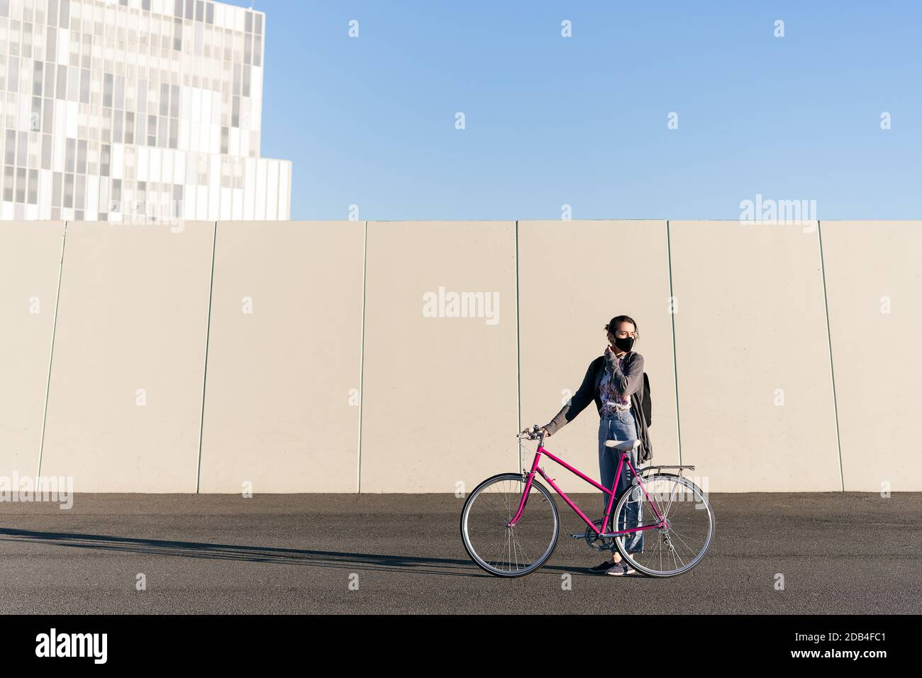 young girl with a pink retro bike at city adjusting her protective mask, concept of active lifestyle, protection against covid and sustainable urban m Stock Photo