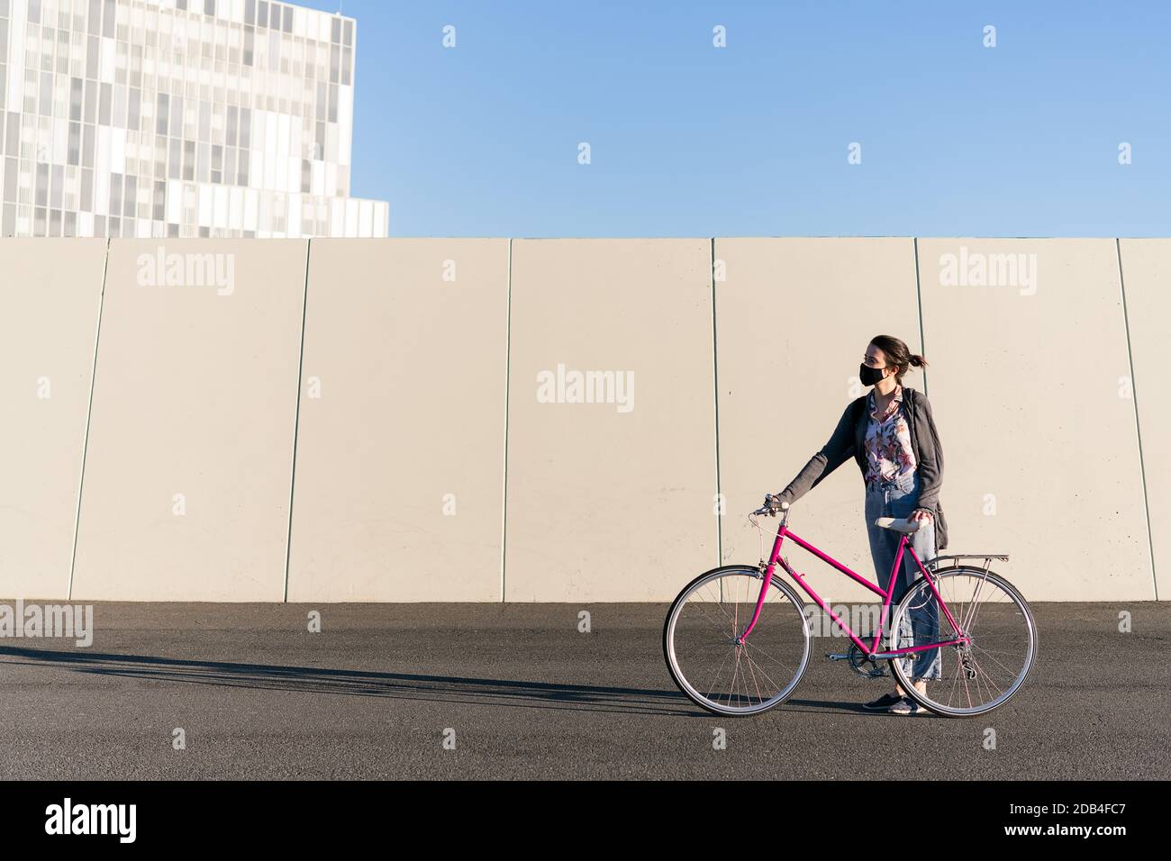 young woman with protective mask standing with a pink retro bike at city, concept of active lifestyle, protection against covid and sustainable urban Stock Photo