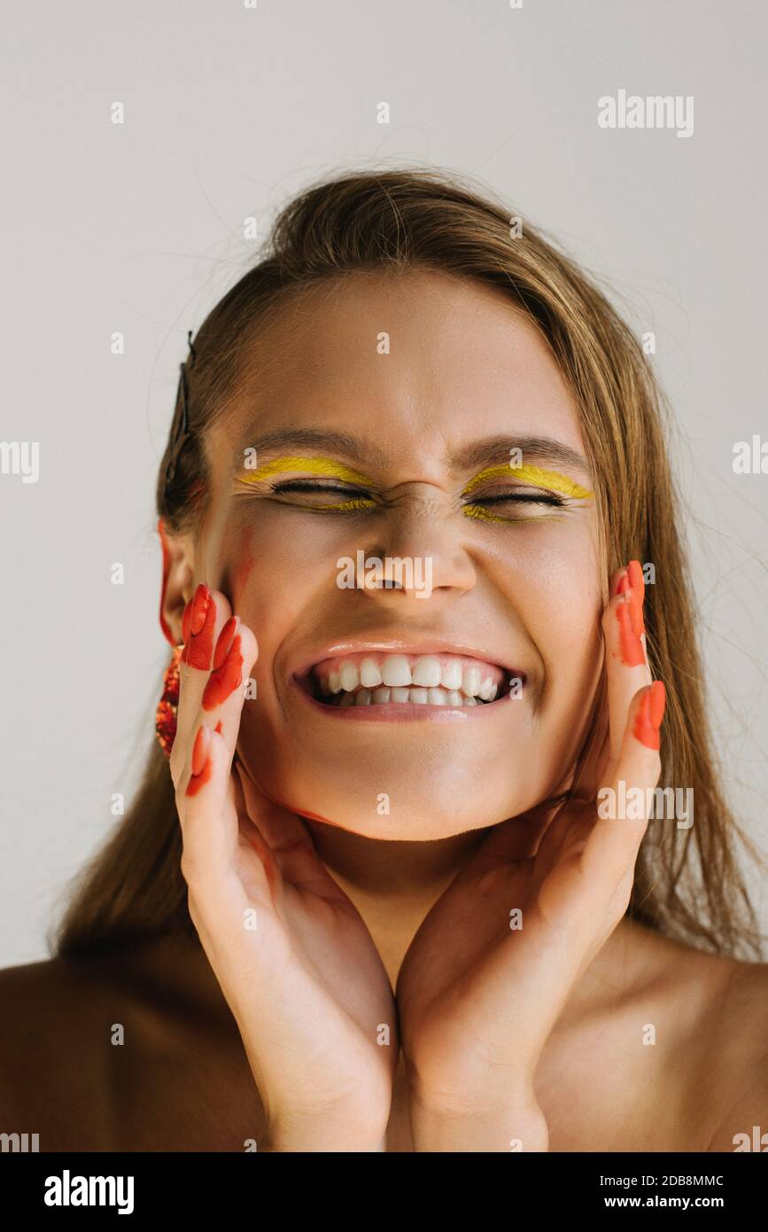 Portrait of a smiling woman wearing unusual make-up Stock Photo