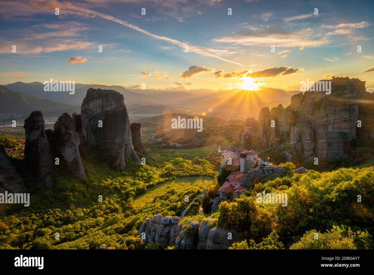 Sunset over monastery of Rousanou and Monastery of St. Nicholas Anapavsa in famous greek tourist destination Meteora in Greece on sunset with sun rays Stock Photo