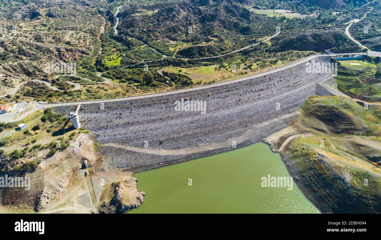 Aerial bird eye view of Kalavasos rockfill dam wall, Larnaca, Cyprus. The street bridge over the reservoir crossing Vasilikos river and the hills arou Stock Photo