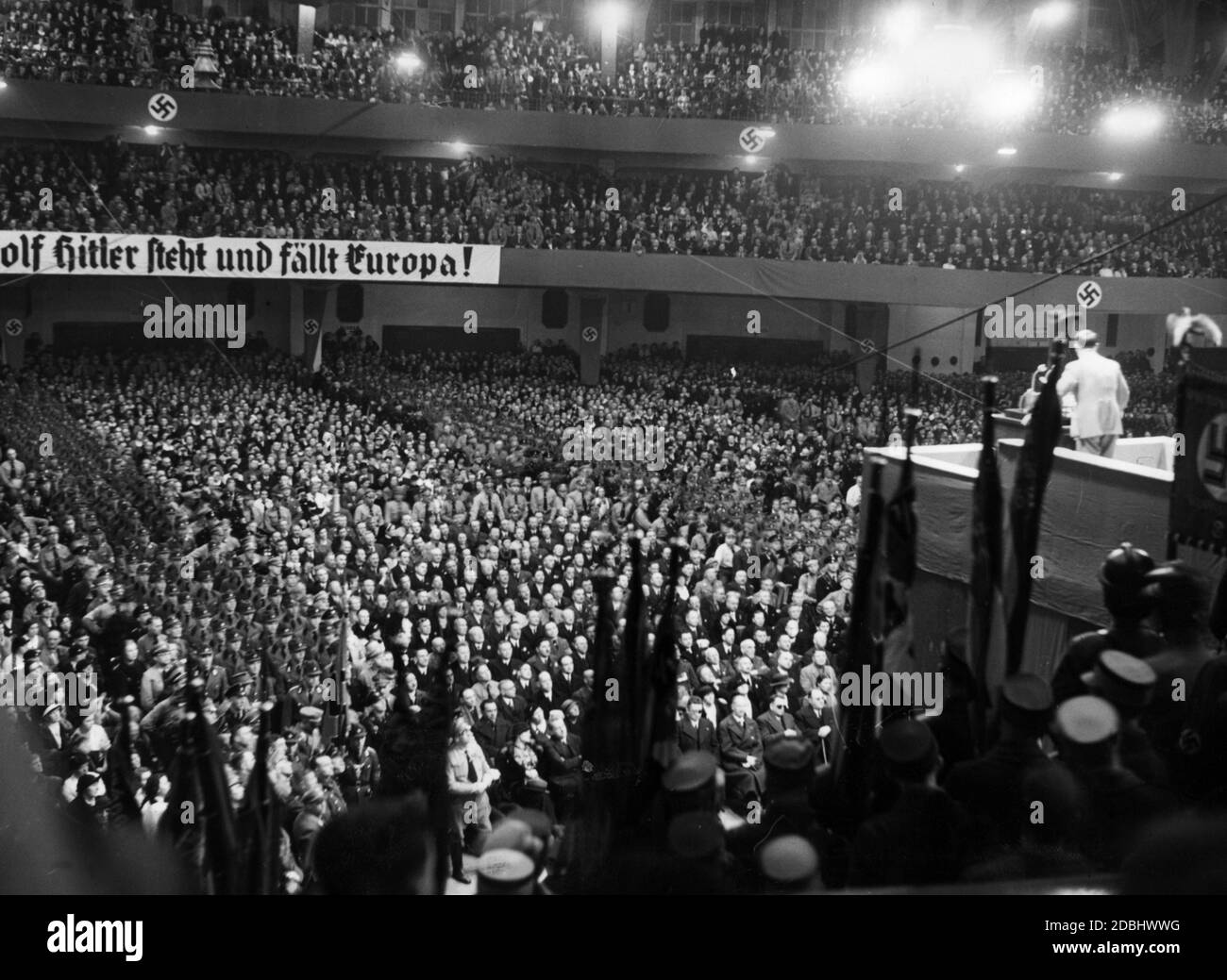 """""""Overview during a speech by Adolf Hitler in the Festhalle in Frankfurt. On the left is a banner reading """"""""Europe stands and falls with Adolf Hitler""""""""."""" Stock Photo"""