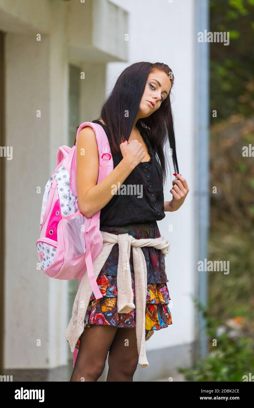 School-girl schoolgirl teengirl is standing before entrance to school isolated looking at camera hand pull pulling hair nercous serious head tilted Stock Photo
