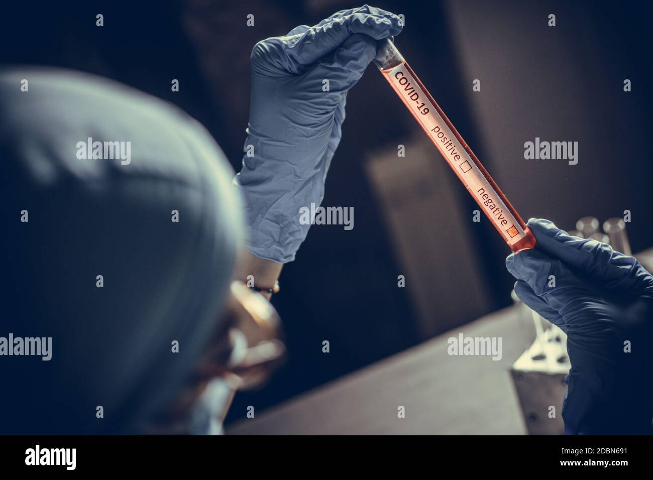 Conceptual photograph of a doctor's hands holding and looking at a test tube while with negative samples for the presence of coronavirus (COVID-19). Stock Photo