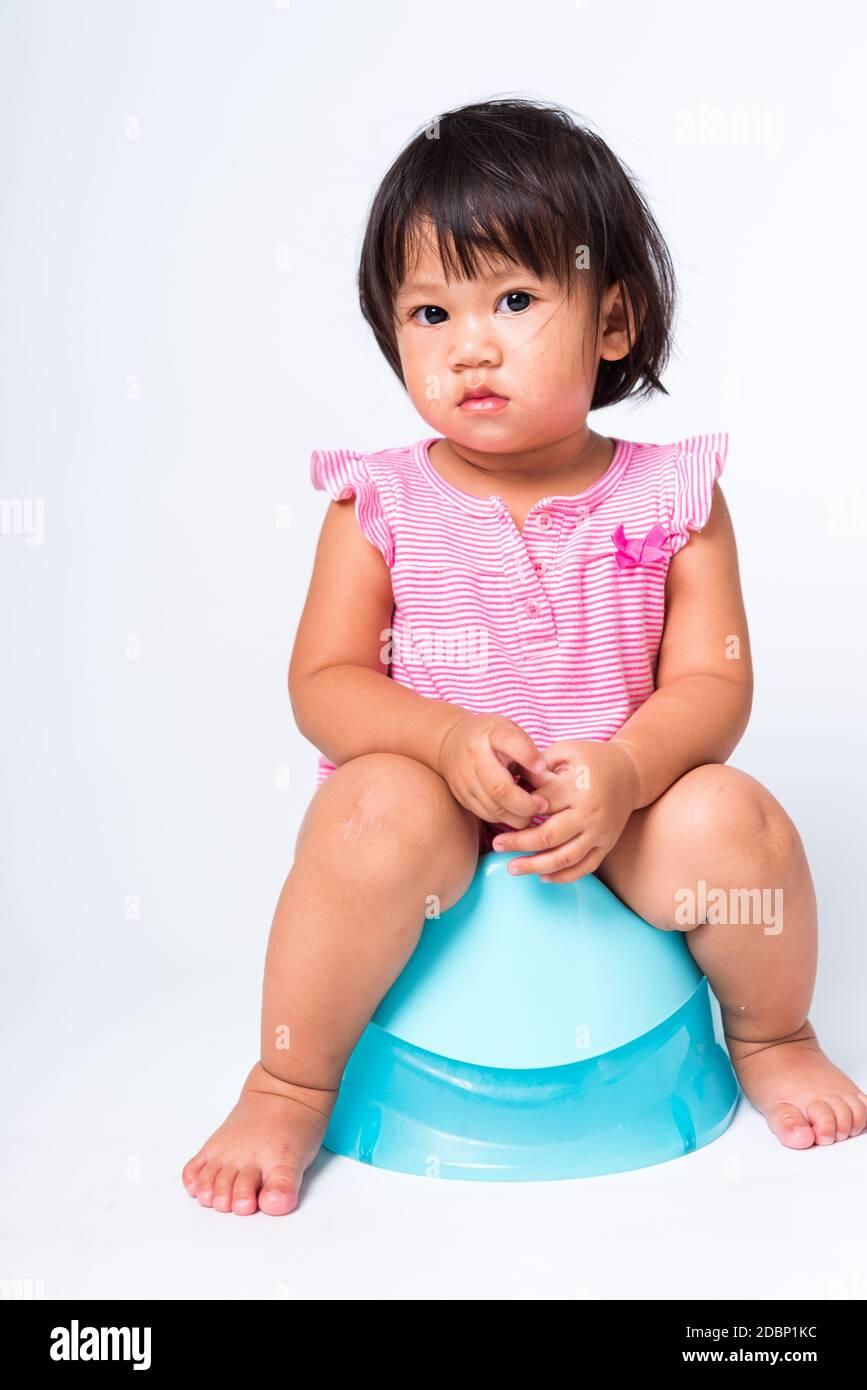 Little girl sitting on toilet training potty on white